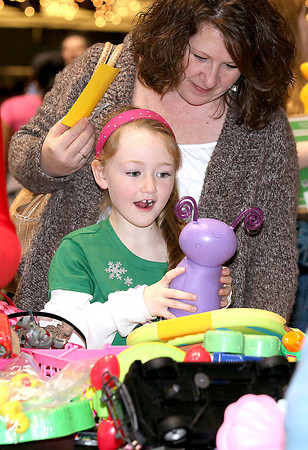 Sarah Smith, 7, finds the perfect toy as her mother, Jessica, looks on during Mac's Toy Party Saturday morning at the Beckley-Raleigh County Convention Center.<br /> Brad Davis/The Register-Herald
