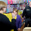 Macie Adkins, 9, of Bolt, center, finds just the right blouse with the help of Amber Lilly, left, wife of Raleigh County Deputy L.T. Larry Lilly, right, during Saturday's Shop with A Cop event at the MacArthur Wal-Mart. F. Brian Ferguson/The Register-Herald