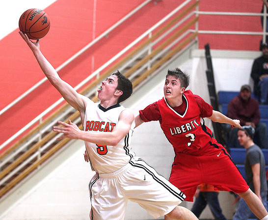 Summers County guard Jacob Lively drives to the basket as Liberty's Devin Acord tries to defend Tuesday night in Hinton.