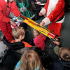 The Volunteer Youth Department had their year-end party on Monday at Winterplace, where children and their parents got to enjoy Santa, gifts and snow tubing. Youth Director Elena Imes, left, helped Santa give out gifts. F. Brian Ferguson/The Register-Herald