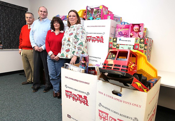 (Left to Right) Toys for Tots local coordinator Jay Quesenberry, MSHA District 12 manager Tim Watkins, his secretary Kathy Day and MSHA volunteer Tammy Walker pose for a quick photo with some of the hundreds of toys workers at the MSHA Mine Academy gathered this year. Toys for Tots was also presented with a $500 donation from Home Safety Association president Bill Wooten Tuesday afternoon.