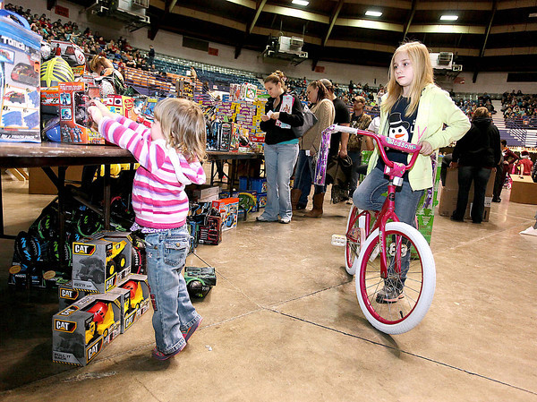Glen Daniel resident Jayden Ransom, 9, keeps an eye on her sister Piper, 2, as she can't resist digging through the various new and used toys available during Mac's Toy Party Saturday morning at the Beckley-Raleigh County Convention Center.<br /> Brad Davis/The Register-Herald