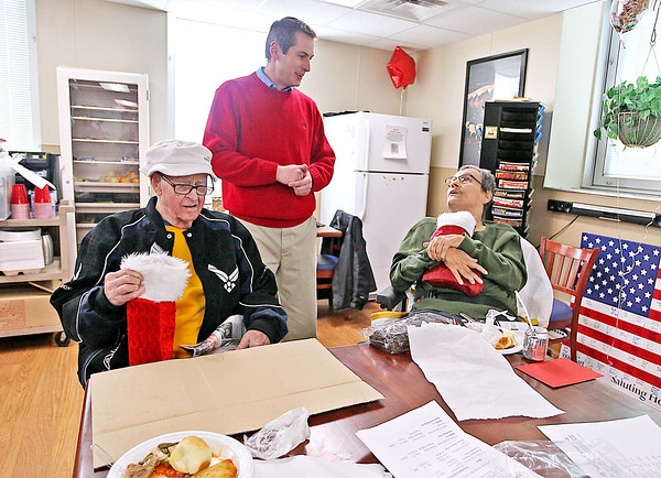 Veterans George Roberts, left, and Robert Castle receive stockings stuffed with gifts from Jon Calfee, middle, of Calfee Funeral Home Wednesday afternoon at the VA Medical Center. <br /> Brad Davis/The Register-Herald