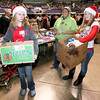 Volunteers McKinley Blankenship (left), 13, and Tori Milam, 13, carry boxes for Porsche Hudson, middle, during Mac's Toy Party Saturday morning at the Beckley-Raleigh County Convention Center.<br /> Brad Davis/The Register-Herald