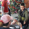 Leeland Mitchell, 8, left, and Hunter Smith, 7, right, get help from Hunter's mother, Donna Smith, center, with decoration of the Christmas Tree during the Volunteer Youth Department's year-end party on Monday at Winterplace.. F. Brian Ferguson/The Register-Herald
