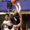 Oak Hill's #25 C. Mills (according to OH site) drives to the basket as Woodrow Wilson's Noah Hancock defends Saturday night at the Beckley-Raleigh County Convention Center.<br /> Brad Davis/The Register-Herald