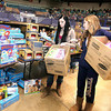 Volunteer Summer Bennett, right, helps Kayla Garris, left, fill up boxes with toys intended for her two children, one a 3-year-old and the other a 3-week-old during Mac's Toy Party Saturday morning at the Beckley-Raleigh County Convention Center.<br /> Brad Davis/The Register-Herald