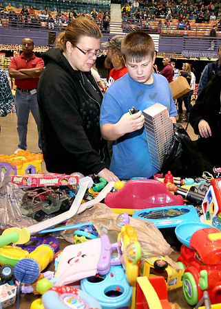 Deanna Hall looks on as her son, 12-year-old Derrick Moore, looks through some of the thousands of toys available during Mac's Toy Party Saturday morning at the Beckley-Raleigh County Convention Center.<br /> Brad Davis/The Register-Herald
