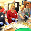 Mary Miller, left, Beth Burns, Christy Columbo and Magan Lasure, volunteers for the United Methodist Temple's 18th annual community church dinner, help put together meals Wednesday from 11 a.m. to 2 p.m. at the Place, directly behind the church.<br /> Rick Barbero/The Register-Herald