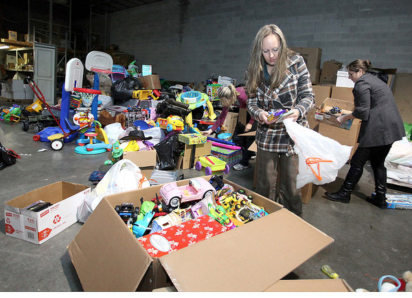 Shady Spring resident and volunteer Kim Dotson sorts through thousands of donated toys as fellow volunteers Kendra Rice (back right) and Tammy Grant (back center) help out Monday night at the BJW Printing warehouse. More than 3000 children will receive the toys at Mac's Toy Fund party Saturday morning at the Beckley-Raleigh County Convention Center.<br /> Brad Davis/The Register Herald