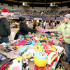 Joyce Kyle, middle, picks out toys for her three children, ages 7, 9 and 11, as she gets a helping hand from fellow mother Porsche Hudson, right, who was picking out toys for her two daughters, aged 3 and 4, during Mac's Toy Party Saturday morning at the Beckley-Raleigh County Convention Center. At left, volunteer David White carries one of Kyle's boxes for her.<br /> Brad Davis/The Register-Herald