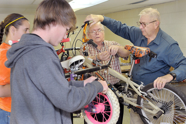 Volunteer work is going at full throttle fixing the donated bikes for the Mac's Toy Fund. (From left), Cara MacAulay, and Thomas Kozer, both of Beckley, work on a childrens bike as part of their confermation from St. Francis de Sales as  Chief Organizer, Arnold Bolen, of Boy Scout Troop 103 and Volunteer Walter Winant, right, lend their expertise on Saturday morning at the Beckley/Raleigh County Convention Center.  F. Brian Ferguson/The Register-Herald