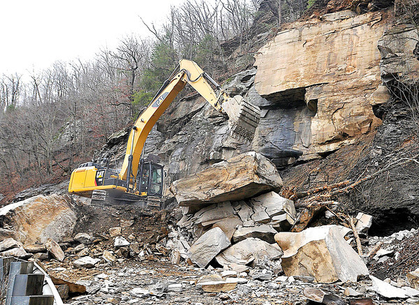 An excavator continues the cleanup effort Monday afternoon at the site of this weekend's massive rock slide that closed a section of Coal River Road between Sundial and Pettry Bottom. Crews had blasted away the largest debris as of Monday, but said lots of work above the slide still remained before the road can be re-opened.<br /> Brad Davis/The Register-Herald