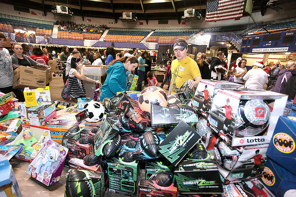 Volunteer Joe Canterbury, middle, helps people find what they want during Mac's Toy Party Saturday morning at the Beckley-Raleigh County Convention Center. Thousands of area kids and parents took home boxes full of new and used toys that are sure to bring many smiles this Christmas. <br /> Brad Davis/The Register-Herald