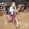 Glen Daniel resident Jayden Ransom, 9, shows off a new bike she picked out for Christmas during Mac's Toy Party Saturday morning at the Beckley-Raleigh County Convention Center.<br /> Brad Davis/The Register-Herald