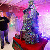 Automotive technology student Adam Lilly shows off his version of a Christmas tree, one made of engine blocks and pistons during the 13th annual Festival of Trees Tuesday night at the Academy of Careers and Technology. Lilly's tree actually starts up and runs, but it can't power your vehicle.<br /> Brad Davis/The Register-Herald