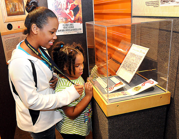 F. BRIAN FERGUSON/THE REGISTER-HERALD=Shantel Rogers, 13, left, and her little sister, Carlella Branch, 6, right, both of Beckley, check out some Confederate Civil War Medals that are part of a new exhibit at the Youth Science Museum.