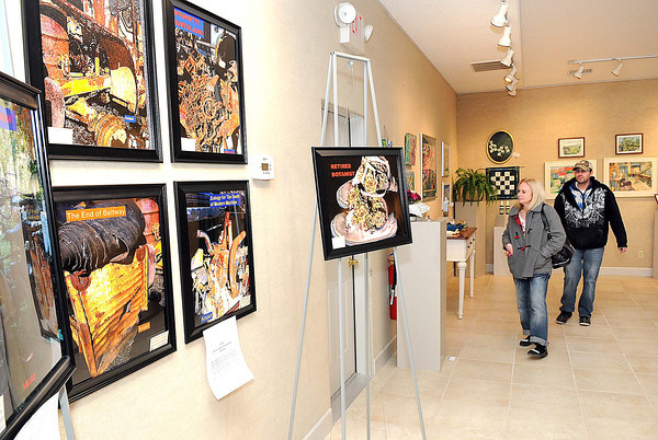 Michelle and Justin Levin, of Beckley, look over the new exhibit at the Cynthia Bickey Art Center on Johnstown road in Beckley Saturday afternoon.<br /> Rick Barbero/The Register-Herald