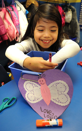 Loren Dysangco pulls a crayon out of a bucket in Kim Simpson's kindergarten class at Stanaford Elementary School. Students made Valentines for Veterans.<br /> Rick Barbero/The Register-Herald