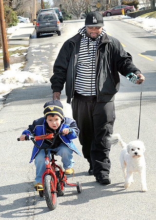 Rashaun Carter, of Beckley, walks down Elkins Street in Beckley Wednesday afternoon with his son, Justyce Carter and his dog katie. <br /> Rick Barbero/The Register-Herald