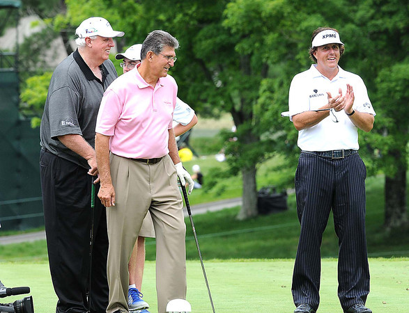 Jim Justice, owner and chairman The Greenbrier Resort, left, US Senator Joe Manchin and Phil Mickelson, react after Jay Justice hit his tee shot on the par 3 third hole within 5ft of the cup during The Greenbrier Classic Pro-Am held on the Old White course Wednesday afternoon.<br /> Rick Barbero/The Register-Herald