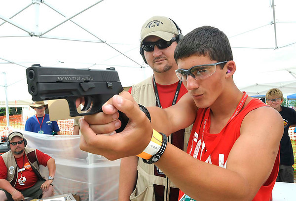 Don Laver, of Summerville, S.C., chartered organization representative troop 9212, left, watches Nolan Lyle, troop C318, of Yelm Washington State, use a 9mm Sig Saver P250 gun at the shooting range State during the National Boy Scout Jamboree at the new Summit Bechtel Family National Scout Reserve in Mt. Hope, WV<br /> Rick Barbero/The Register-Herald