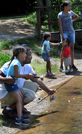 Alanna Penn, 6, gets some fishing tips from her father, Blake Penn as the rest of the Penn family, Amiya, Ayden, and mother, Jennifer, all of Beckley, look on during a Friday fishing trip to Little Beaver State Park. F. Brian Ferguson/The Register-Herald