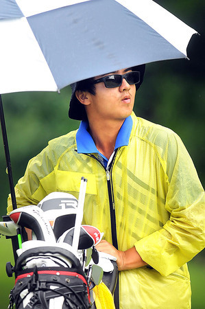 Zecheng Dou, tries to stay dry on the 17th hole on the cobb course at The Resort at Glade Springs during the Greenbrier Classic PGA Tour Pre-Qualifer.<br /> Rick Barbero/The Register-Herald