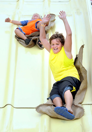 Tripp, 4, left, and Tristan Stiffler, 11, of Meadow Creek, take a ride on the Super Slide during the Friends of Coal Auto Fair.<br /> Rick Barbero/The Register-Herald