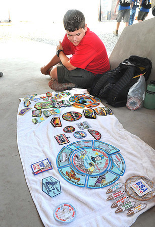 Brian Bordelon, troop B421, of Batonrouge, La, look over his patches he wants to trade at the Boy Scout Jamboree Friday morning at the new Summit Bechtel Family National Scout Reserve near Glen Jean, WV<br /> Rick Barbero/The Register-Herald