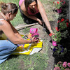 Casinda Nelson, left, and Jenny Curry, both with One Voice, a Faith-Based Community Resource, plant some flowers in front of their facility on South Kanawha Street on Tuesday afternoon. F. Brian Ferguson/The Register-Herald