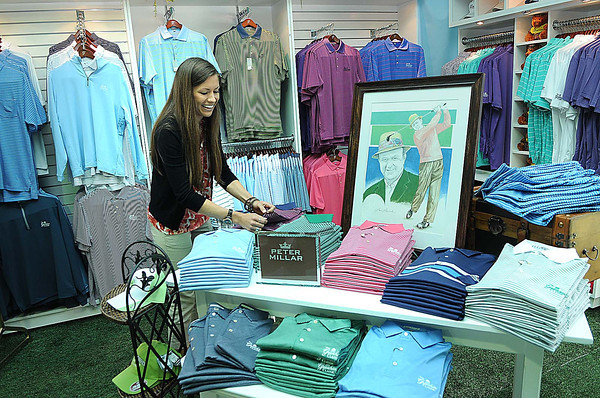 Liz Ferrelle, marketing specialist with Peter Millar, looks over shirts in the merchandise tent Monday during The Greenbrier Classic Pro-am.<br /> Rick Barbero/The Register-Herald