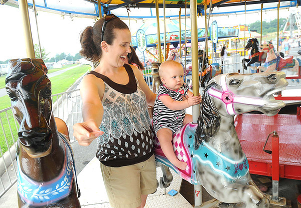 Meredith Stover rides the carousel with her daughter Addison, 11 months, during the Friends of Coal Auto Fair.<br /> Rick Barbero/The Register-Herald