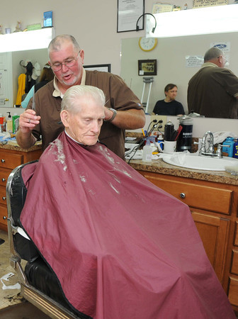 Rex Farmer, owner of Rex's Barbershop in Crab Orchard, gives William Foley a free haircut. They were celebrating fathers day and fatherhood.<br /> Rick Barbero/The Register-Herald