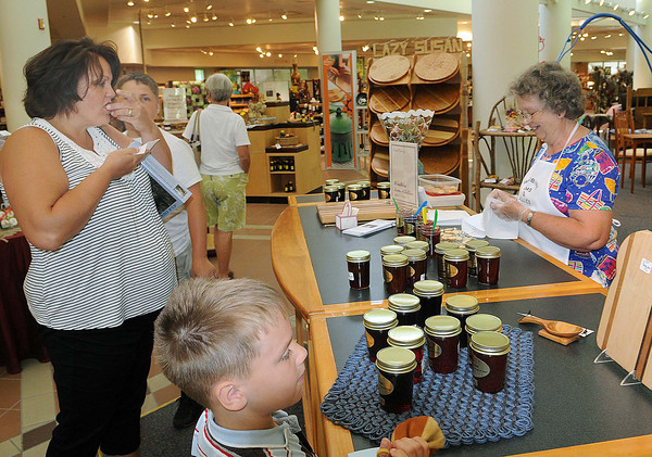 Anna Dickerson, left, and her son Paul, 6, center, try some of Levada Hodovan Woodbine Jams & Jellies at Tamarack on Saturday. Hodovan and her associate. Libby Deitz make the product on their Richwood farm and is named for the C.C.C. camp near her home. F. Brian Ferguson/The Register-Herald