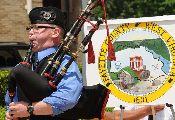 Andrew Branard, pipe sergeant Kanawha Pipes & Drums, plays Amazing Grace in front of the Fayette Co. Courthouse in Fayetteville during the celebration of Fayette County's new seal and flag.<br /> Rick Barbero/The Register-Herald