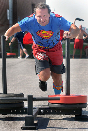 It's a Bird... It's a Plane=Chip Williams, of Beckley, celebrates his 39th birthday on Saturday by pushing a weighted sled across the parking lot of L.A. East Fitness. Williams fellow Beckley Crossfit members made him wear the Superman costume to mark his special day.  F. Brian Ferguson/The Register-Herald