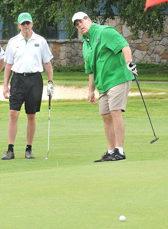 Jim Hamrick, left, watches his son, Mike Hamrick putt on the par 4, 18th hole at Grandview Country Club during the Big Green golf outing.<br /> Rick Barbero/The Register-Herald