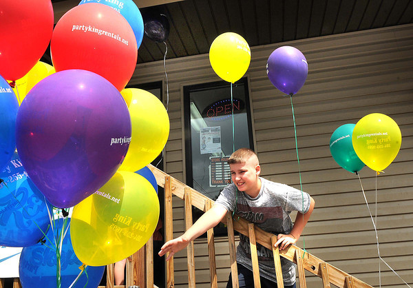 Dakota Clayton, of Fairdale, reaches for a balloon after getting a free haircut at Rex's Barbershop in Crab Orchard. <br /> Rick Barbero/The Register-Herald