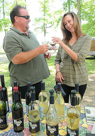 Mike Canterbury, left, and Joanna Sheppard, of Crab Orchard, tap their wine glasses together during the 15th annual West Virginia Spring Wine Festival at Daniel Vineyards in Crab Orchard.<br /> Rick Barbero/The Register-Herald