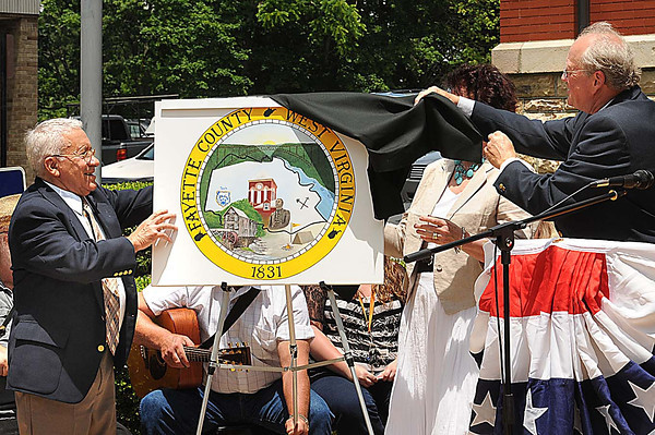 Fayette County Commissioners John Lopez, left, Denise Scalph and Matthew Wender unviel the new county seal in front of the courthouse in Fayetteville Saturday afternoon.<br /> Rick Barbero/The Register-Herald