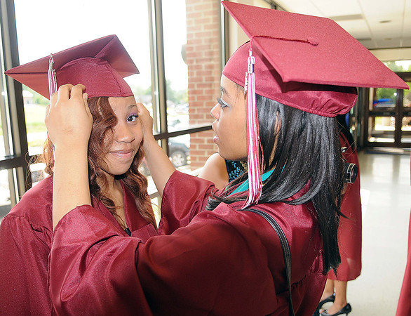 Woodrow Wilson seniors Jasmin Maniece, left, and Iyana Wynne, right, make some final adjustments before their graduation at the Beckley-Raleigh County Convention Center. F. Brian Ferguson/The Register-Herald