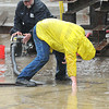 Russell McBride, technician, A.L. Lee Corporation, cleans away debris from a storm drain at A.L. Lee Corporation on Whitestick Street in Mabscott. Watcing in background is John Snuffer, plant manager.<br /> Rick Barbero/The Register-Herald