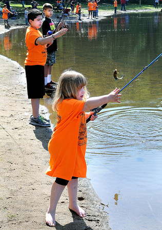 Ashleigh Bowling, 5, of Beckley, casts her line as other children reel in fish during Saturday's Kids Fishing Derby at Little Beaver State Park. F. Brian Ferguson/The Register-Herald