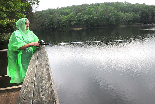 Sherry Hill, of Lynco, stays covered up during a slight rain fall at Little Beaver State Park trying to catch a few fish. <br /> Rick Barbero/The Register-Herald