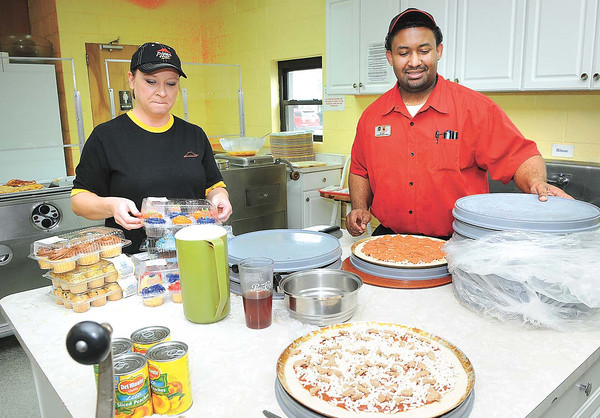 Pizza Hut managers, Crystal Bradford, Rainelle left, and Blake Penn, Sophia, help out at Carpenter's Corner on Prince Street in Beckley.<br /> Rick Barbero/The Register-Herald
