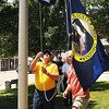 Donnie Ballard, left, and Dickie Smith, both with Fayette County Courthouse maintenance Department, raise the new flag in front of the Fayette Co. Courthouse in Fayetteville during the celebration of Fayette County's new seal and flag.<br /> Rick Barbero/The Register-Herald