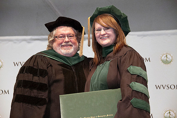 Photo courtesy West Virginia School of Osteopathic Medicine<br /> Newly minted doctor Kelly Lopez stands with her father, David Allen, who was the first graduate of West Virginia School of Osteopathic Medicine 35 years ago.