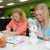 Melanie Harvey, of Hinton, left, and her daughter Emma Ellis, of Shady Spring, work on items at the Pottery Place at Galleria Plaza in Beckley.<br /> Rick Barbero/The Register-Herald