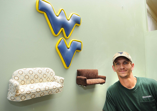 Richard Newsome with wall art at Interior Concepts.<br /> Rick Barbero/The Register-Herald